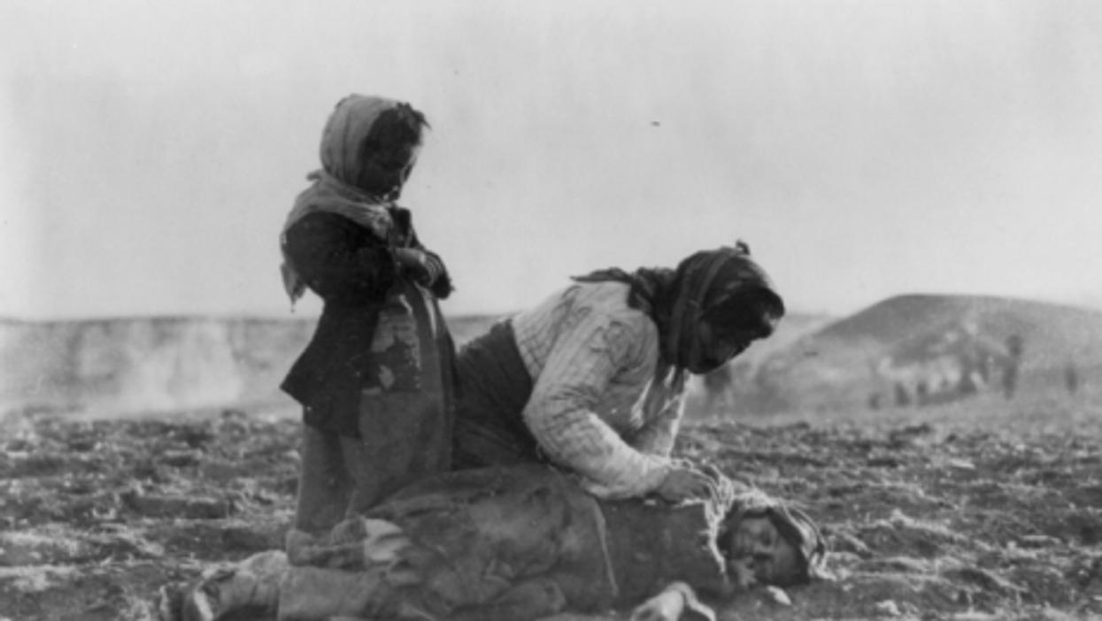 1915: Armenian woman kneeling beside dead child