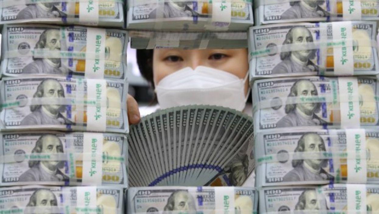 A bank clerk scrutinizes $100 US banknotes in Seoul, South Korea.