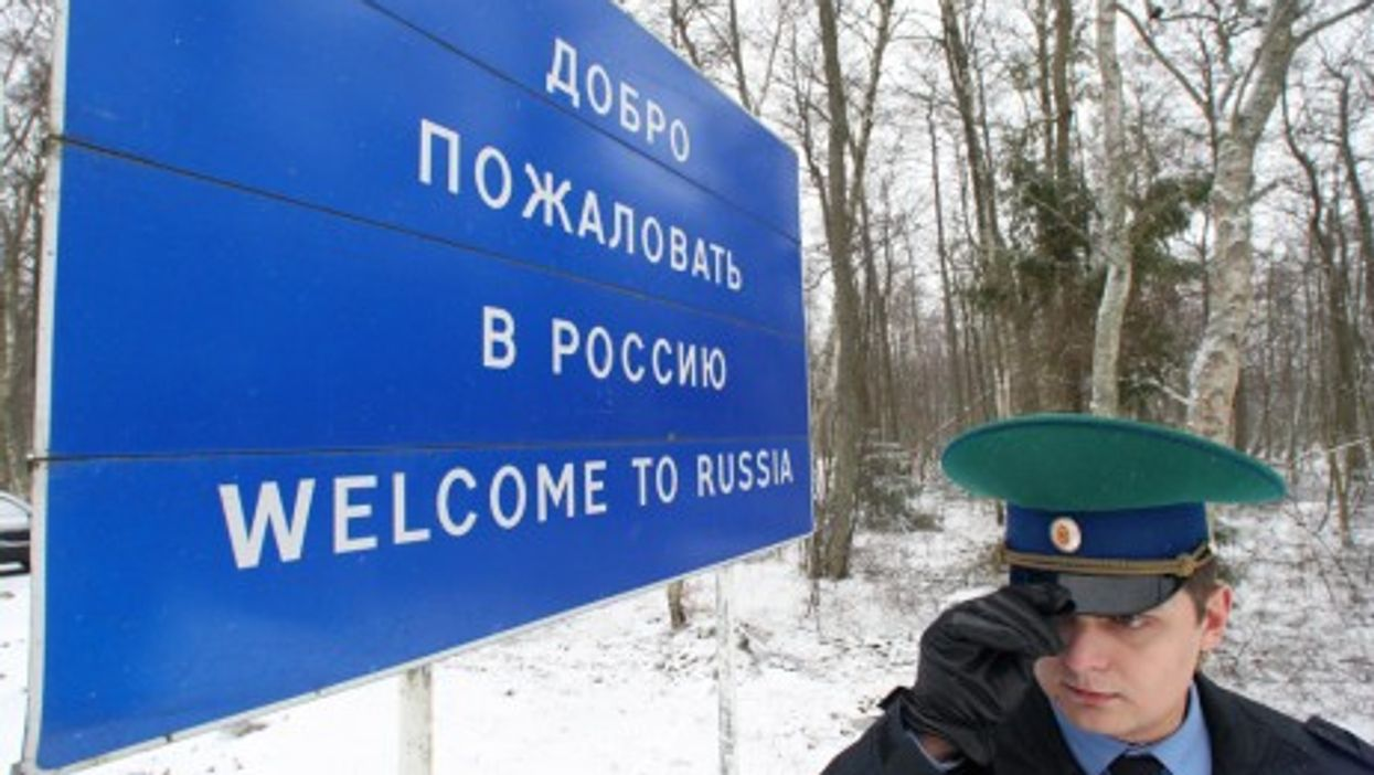 """A border guard at a """"Welcome to Russia"""" sign"""