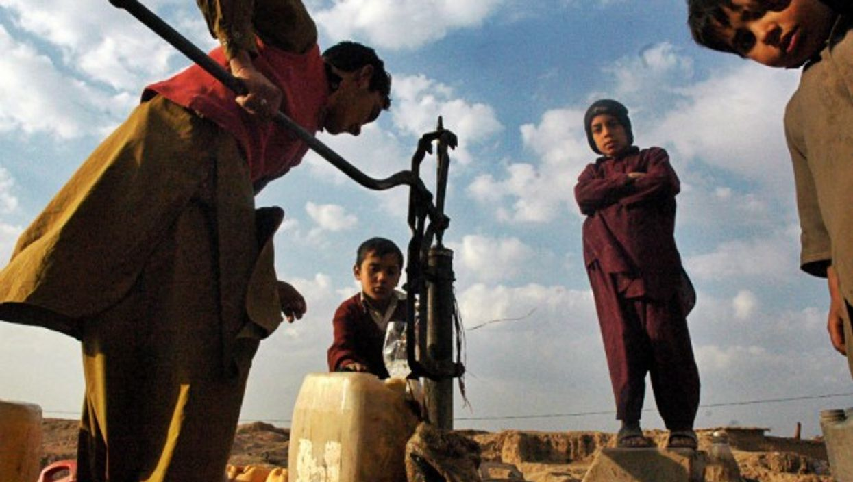 A boy filling water jugs on the outskirts of the capital of Pakistan