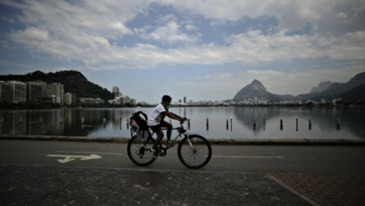 A boy peddles past the polluted  Rodrigo de Freitas lagoon slated to be the site of sailing events at Rio 2016.