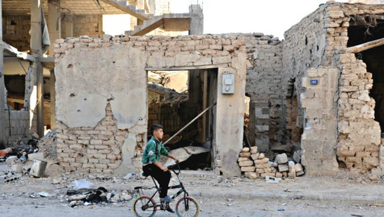 A boy rides a bicycle amid rubble in Homs