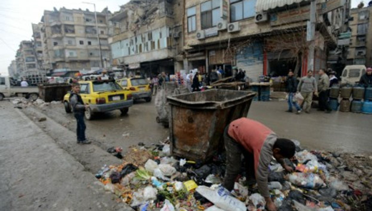 A boy searches in a pile of garbage for something to eat in Aleppo.