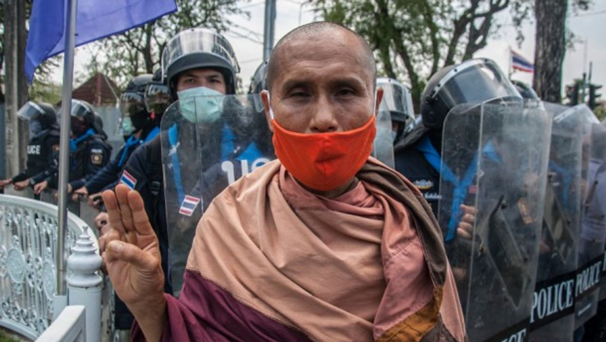 A Buddhist monk makes the three finger salute during pro-democracy protests in Bangkok, Thailand.
