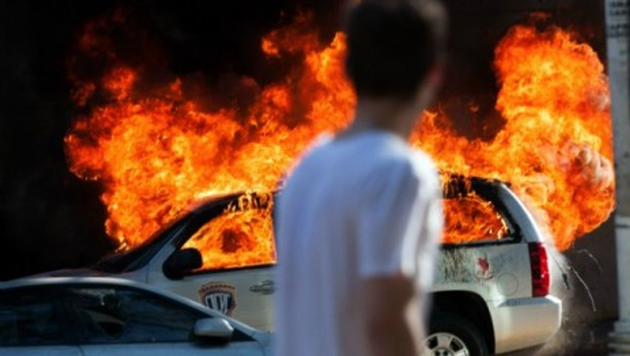 A car burns during clashes between students and police during anti-government protests in Venezuela.
