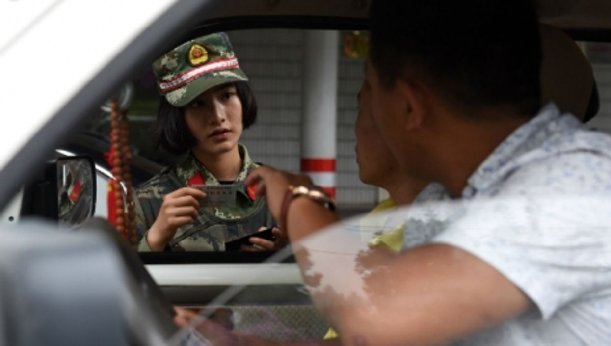 A Chinese anti-drug soldier inspects a car in the southwest Yunnan province, on June 24, 2015