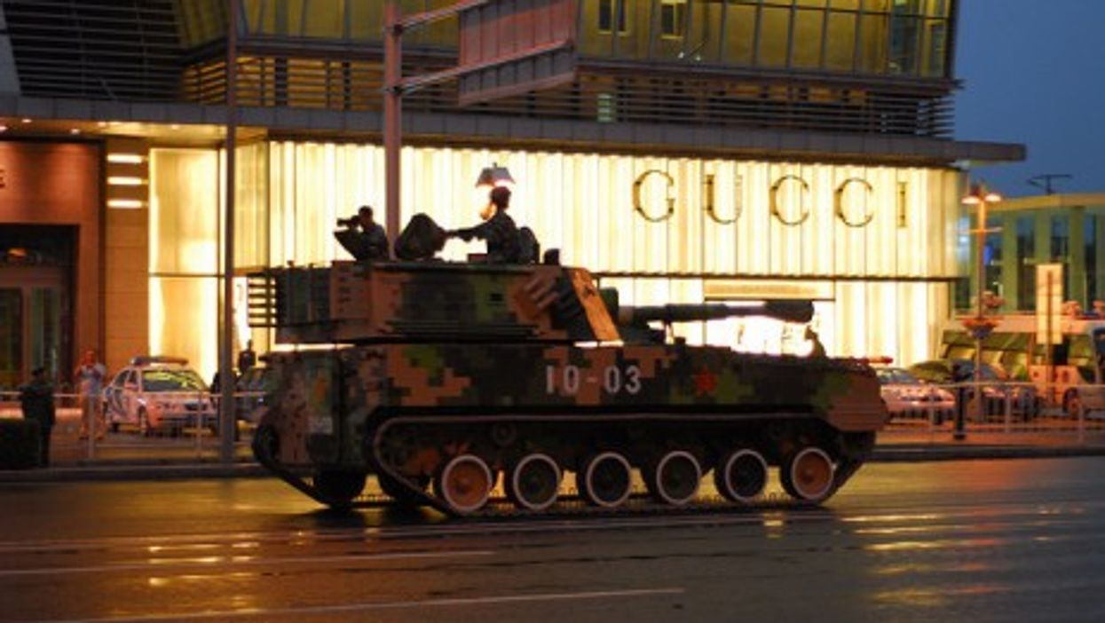 A Chinese tank rolls past a Gucci store in Beijing (gadgetdan)