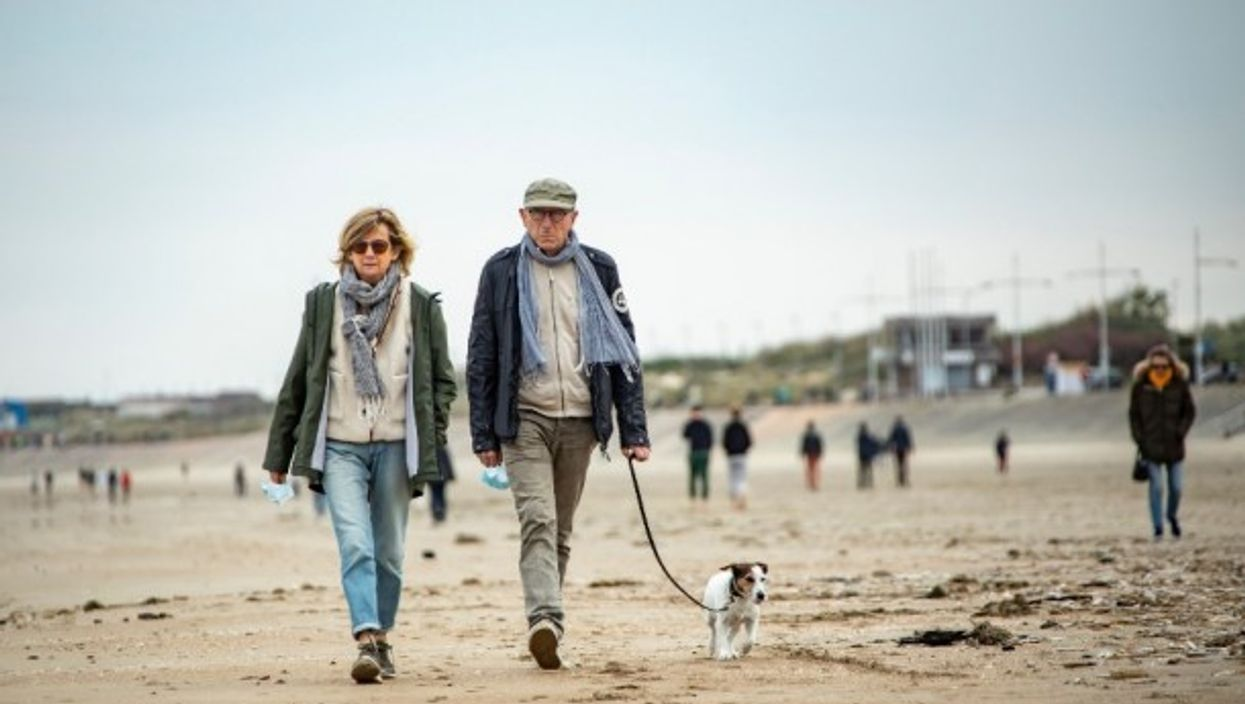 A couple walks on a beach in Dunkirk, France.