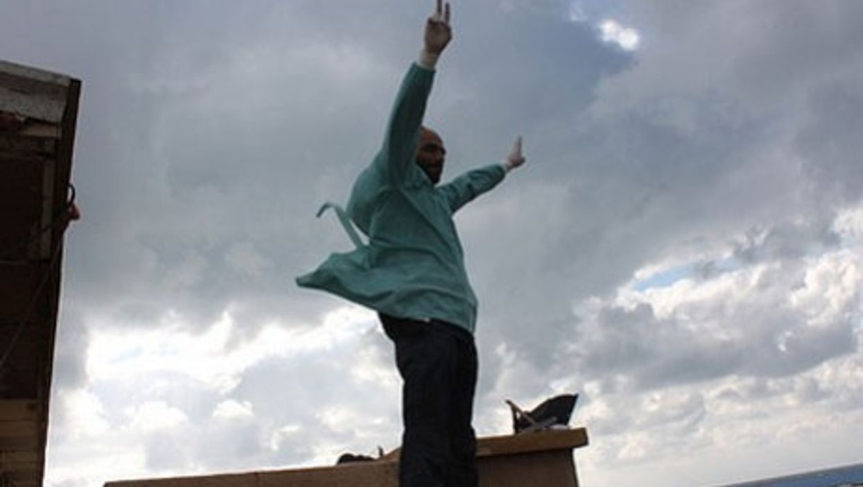 A doctor last month waves the Victory sign atop the Benghazi courthouse