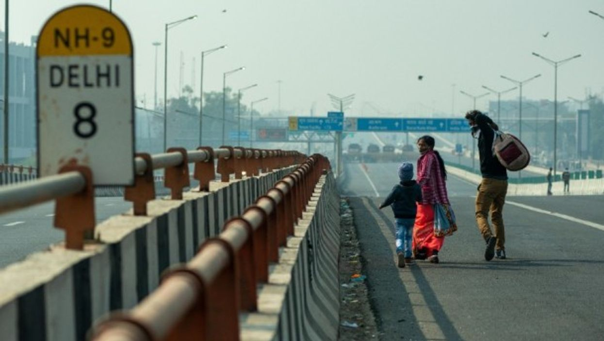 A family walking on an empty road towards Delhi in December 2020, amid farmers' protests against the government's new agricultural reforms.