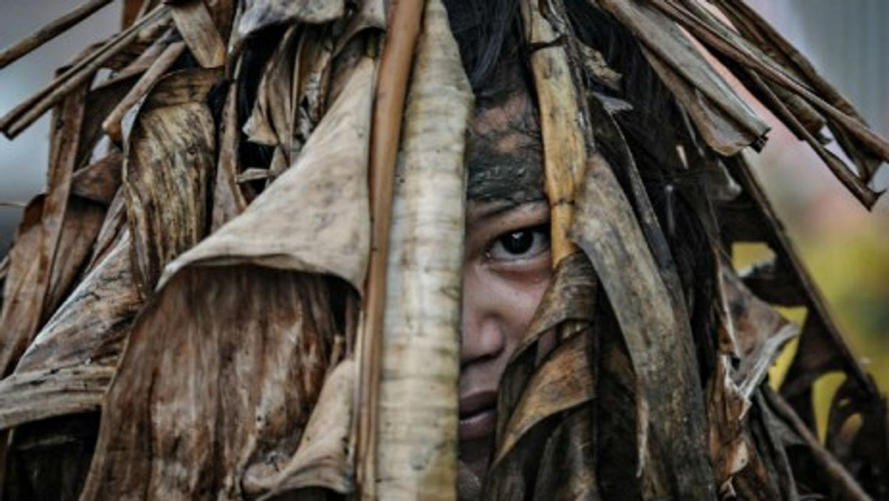 A Filipino devotee is covered in mud and dried leaves during a religious tradition marking the Taong Putik festival in northern Philippines.