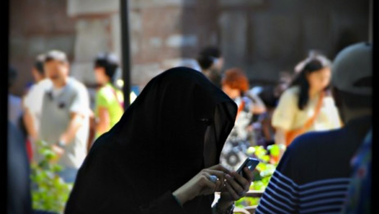 A fully veiled woman using her smartphone in Istanbul