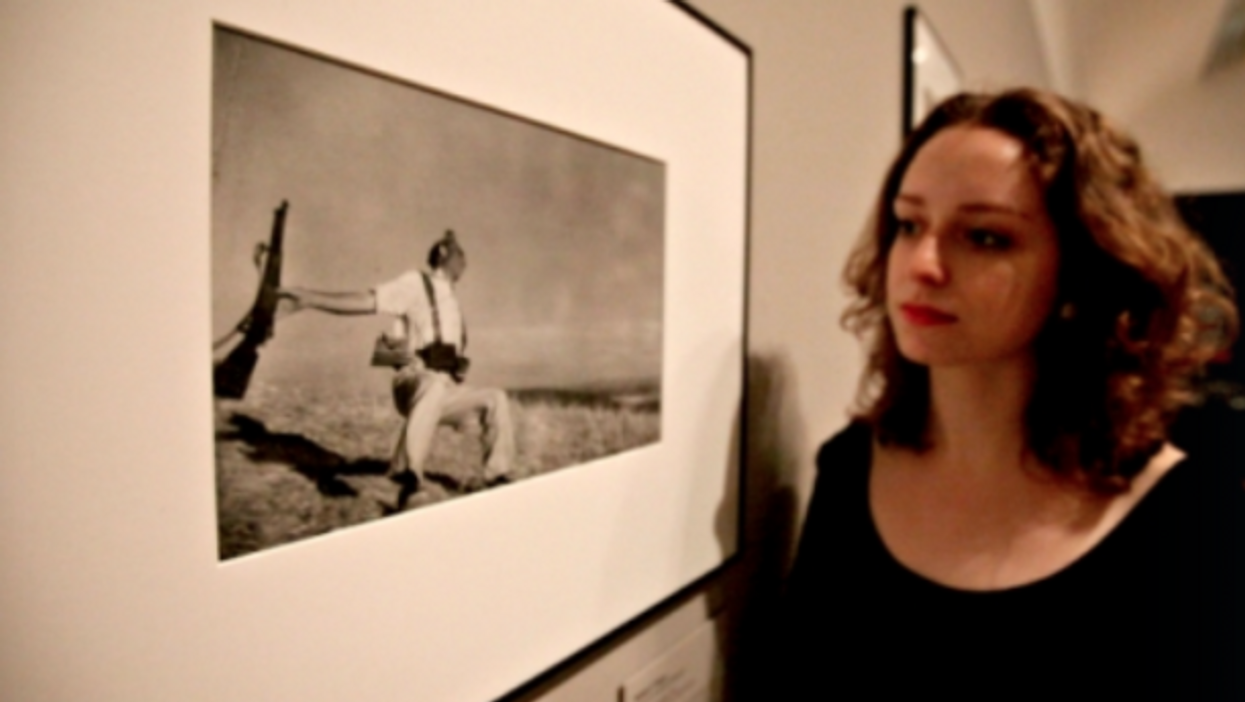 A gallery assistant looks at Robert Capa's