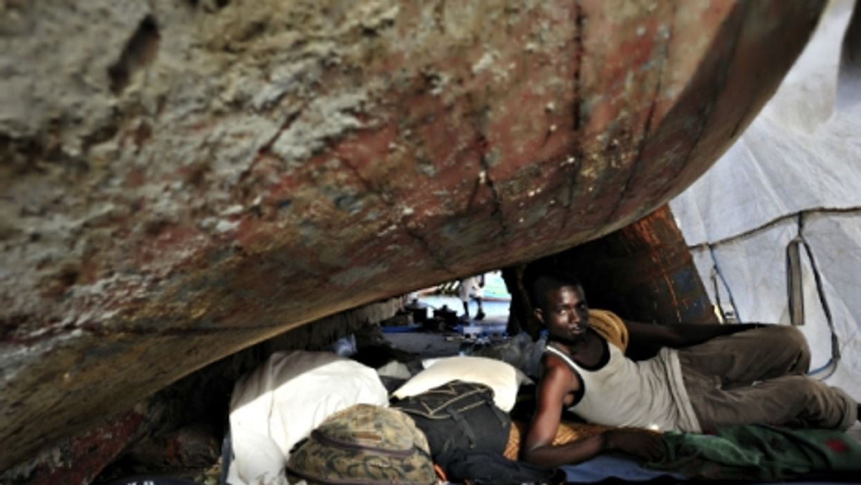 A Gambian migrant living under an boat outside Tripoli, Libya