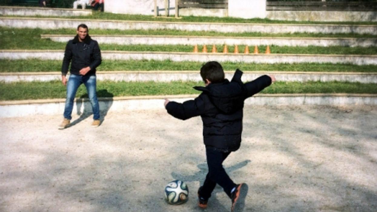 A Garrigan boy playing soccer with a Syrian refugee in Paris' Parc Sainte-Perrine