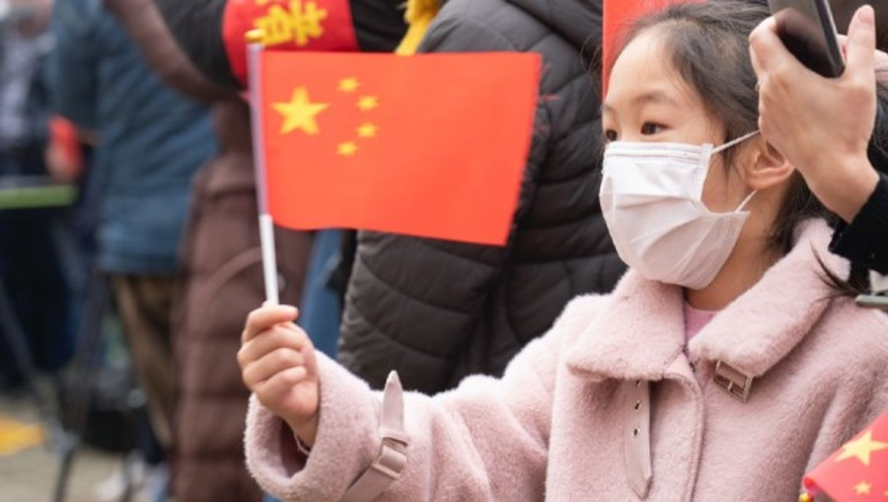 A girl waves a Chinese flag while seeing off visiting medics from in Wuhan on Monday.
