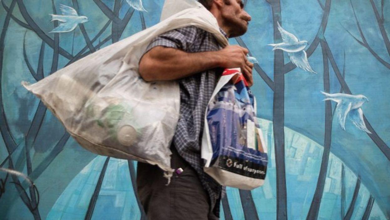 A homeless man walks past a mural in Tehran, Iran.