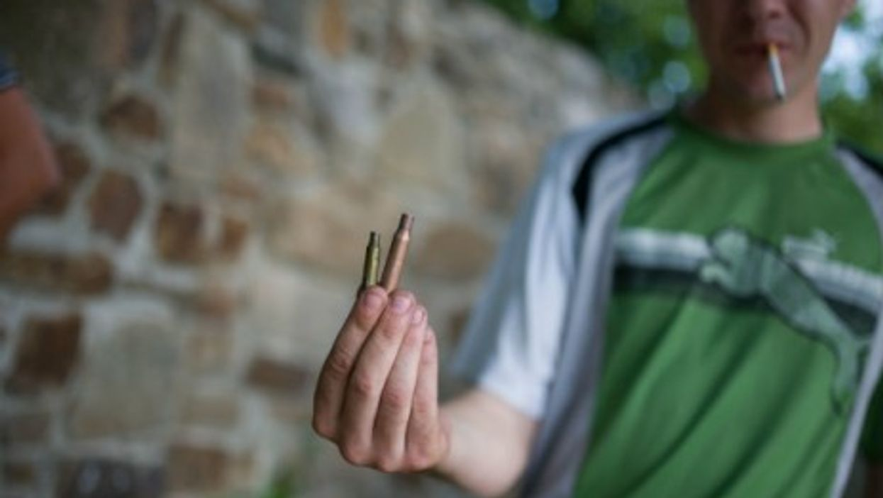 A  local resident shows a shell case on the outskirt of Lysychansk in Donetsk region.