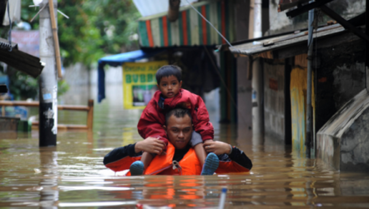 A man carries a child in the floodwaters that have hit Jakarta this week.