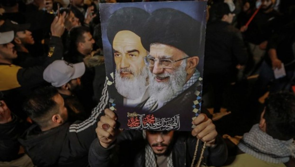 A man carries a poster of the Ayatollahs Khamenei and Khomeini.