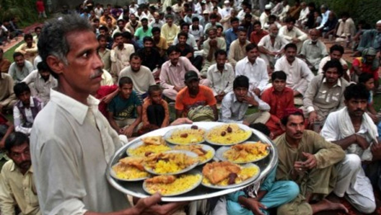 A man distributes Iftar food to Muslim devotees waiting to break their fast during the sacred fasting month of Ramadan.