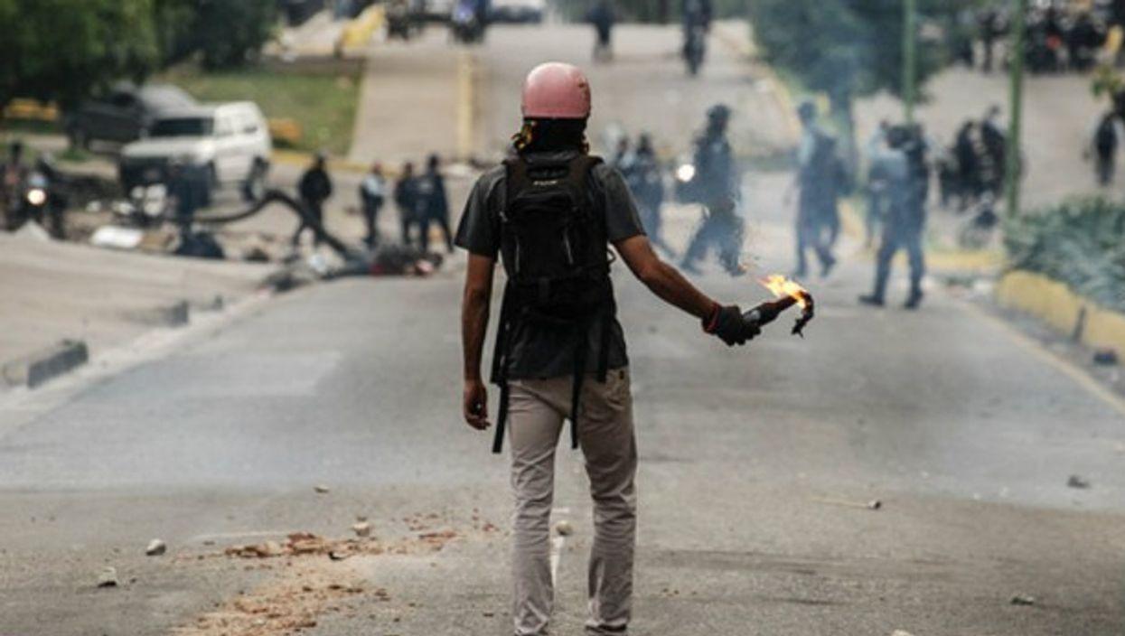 A man holding a molotov cocktail during clashes in Valencia, Venezuela