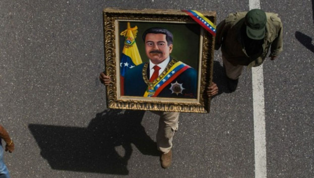 A man holding a portrait of Maduro during a rally on May 1