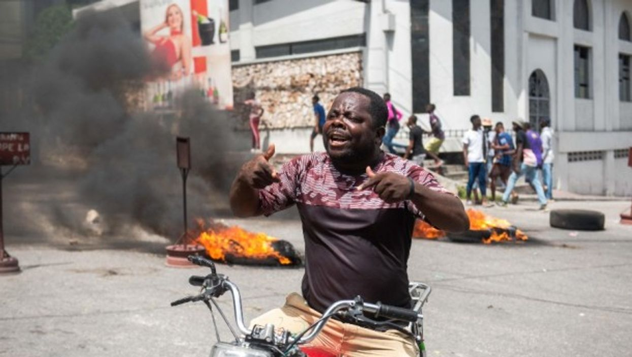 A man protests in the streets of Port-au-Prince after the assassination of President Moise