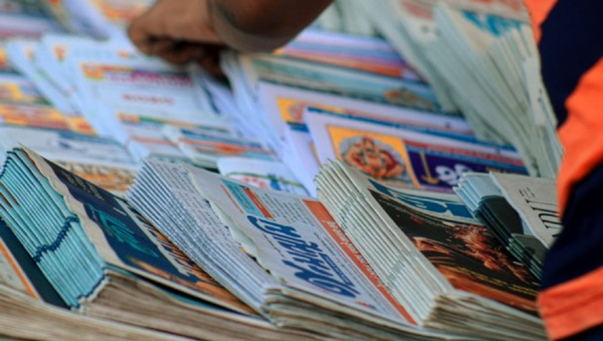 A man searches through stacks of newspapers.