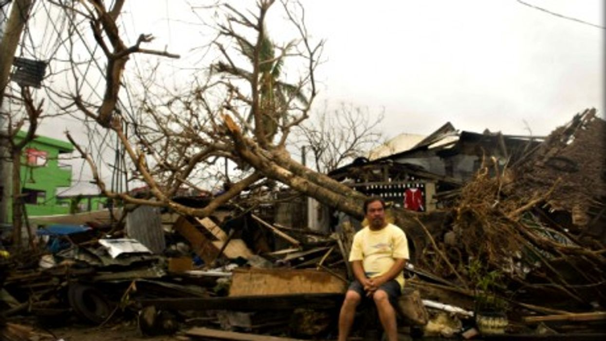 A man sits on debris of his house in Leyte province, central Philippines