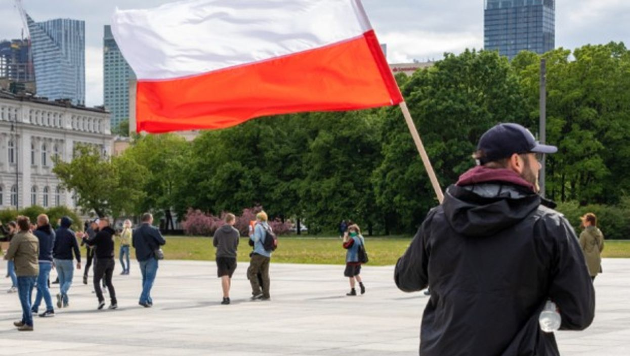 A man stands with the Polish flag during a National Entrepreneur strike in Warsaw, Poland.