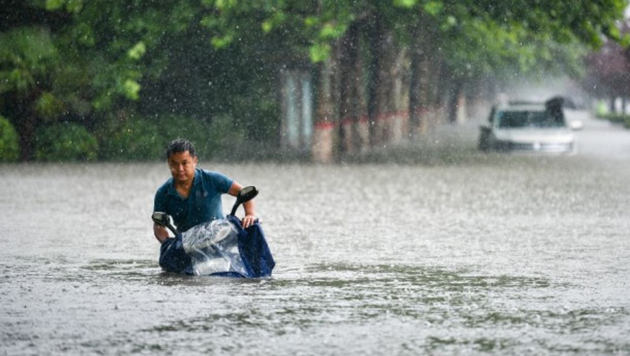 A man wades with his motorbike through Zhengzhou, central China, where thousands were evacuated and a dozens killed following record rains