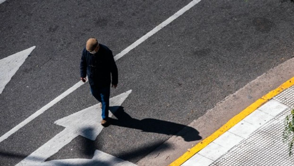 A man walked down the street wearing a mask in Buenos Aires.