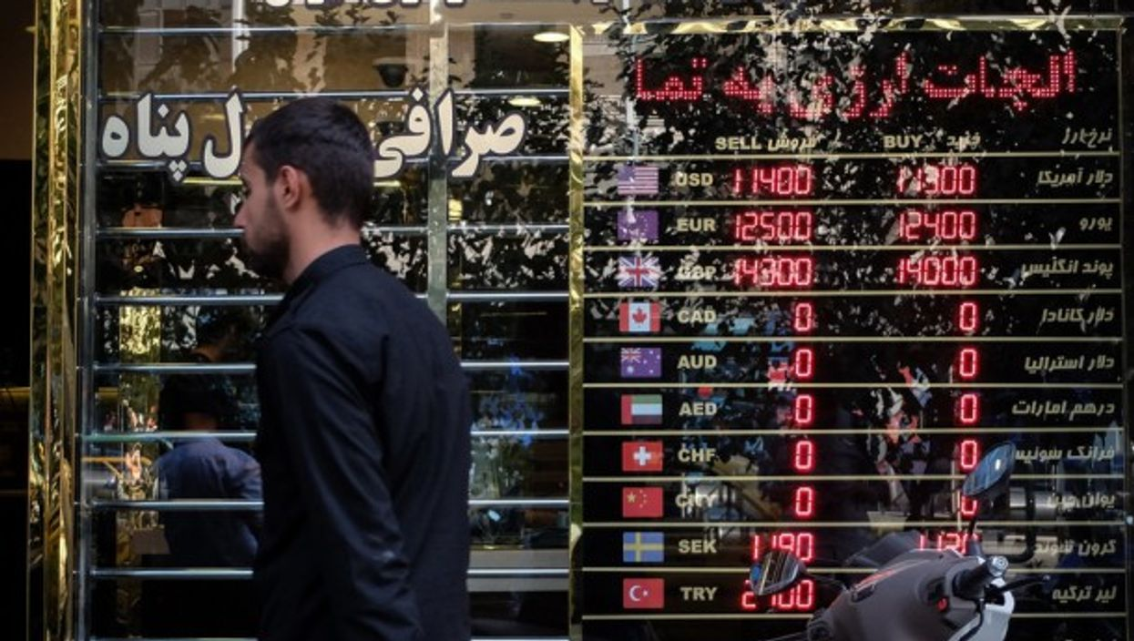 A man walking past a currency exchange shop in Tehran