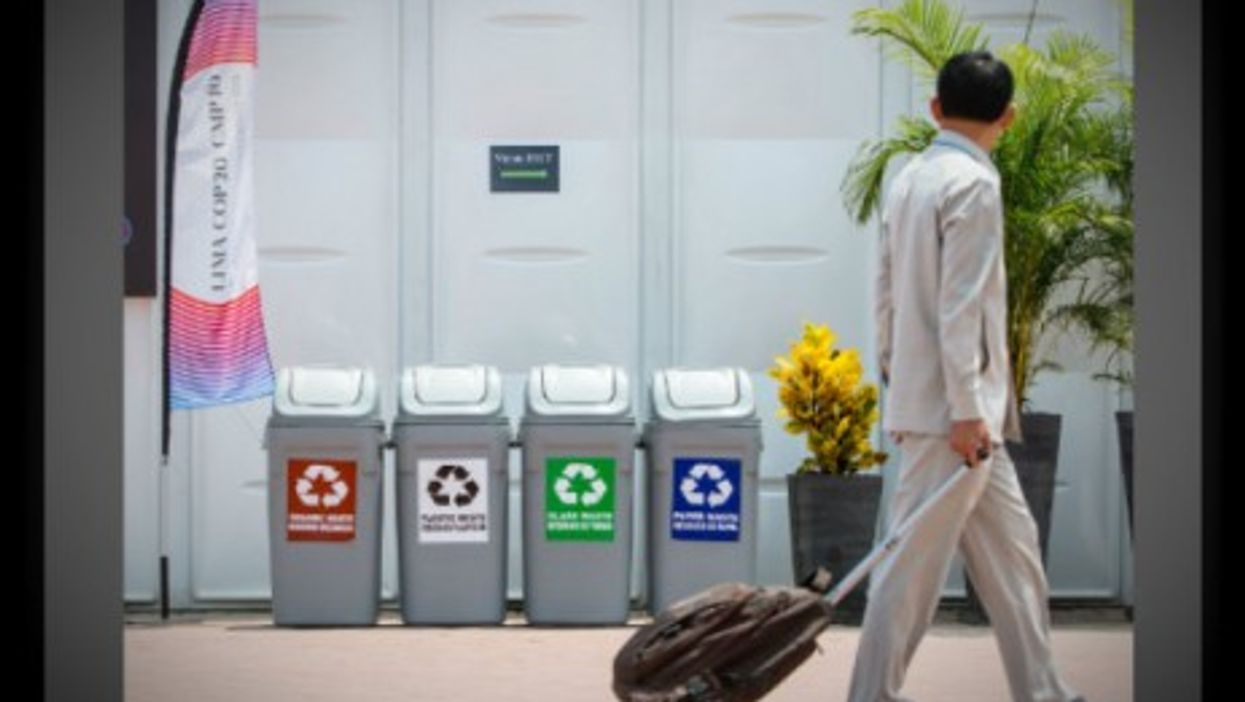 A man walks past recycling bins next to the COP 20 conference center in Lima on Dec. 3