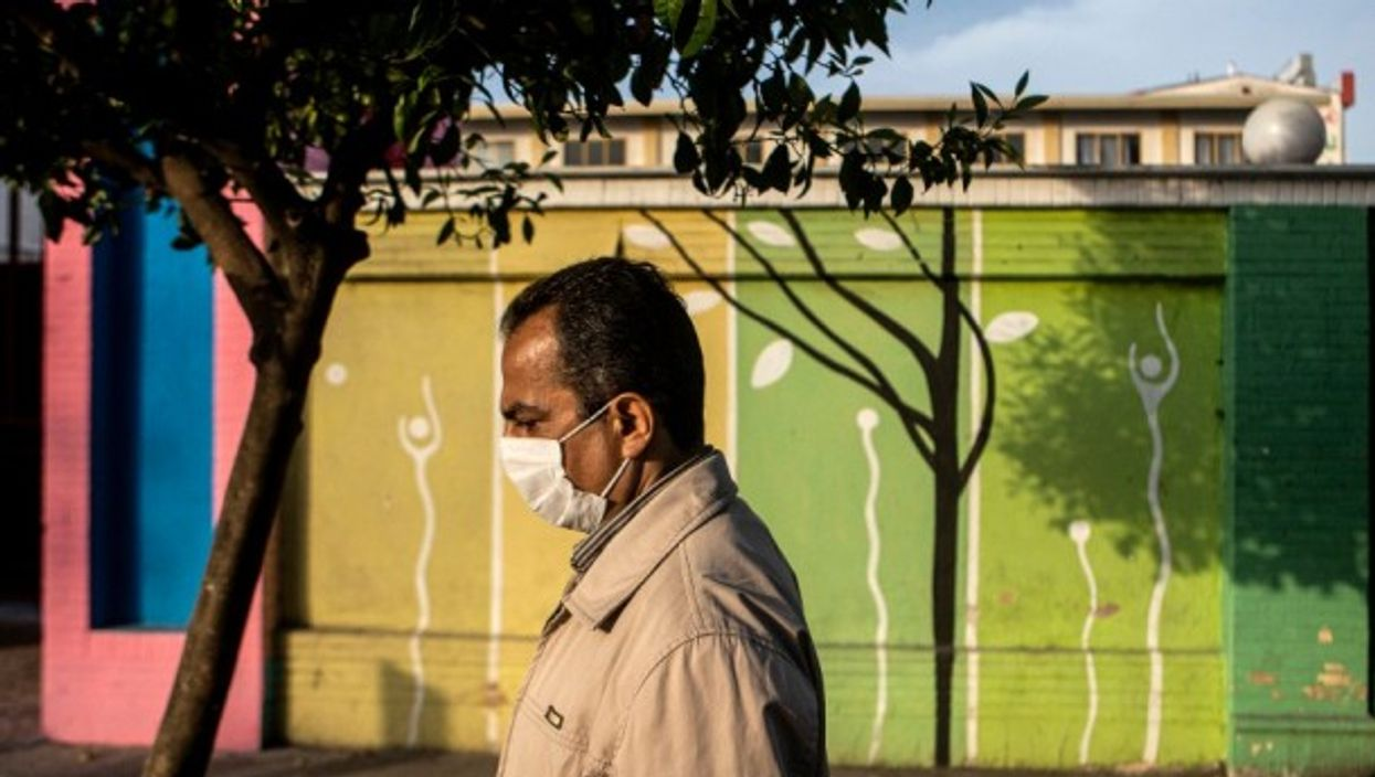 A man wearing a face mask walks on a street in Tonekabon, Iran, on April 26, 2021.
