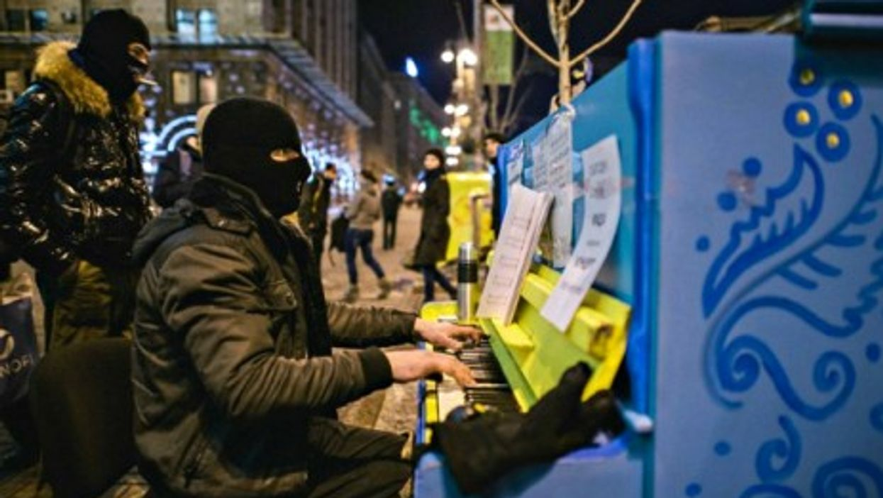 A masked protester plays the piano in front of Kiev's occupied City Hall