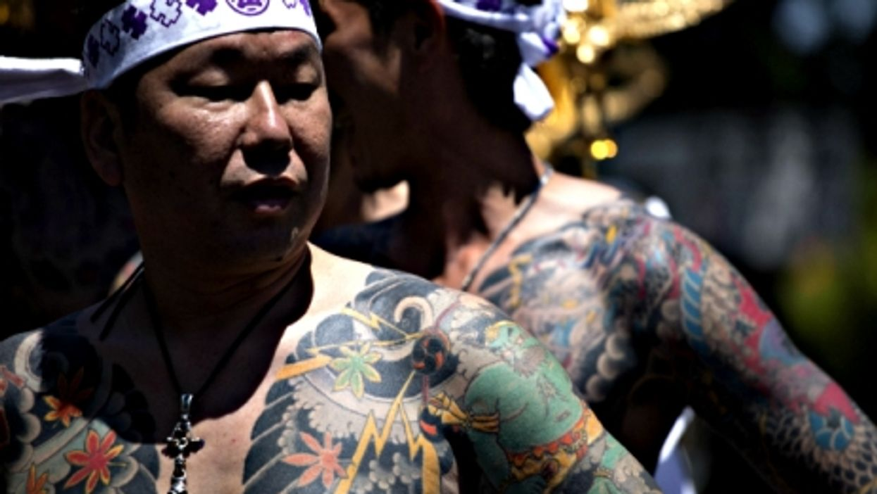 A member of the Yakuza shows off his tattoos during the Sanja Matsuri in Tokyo, 2014.