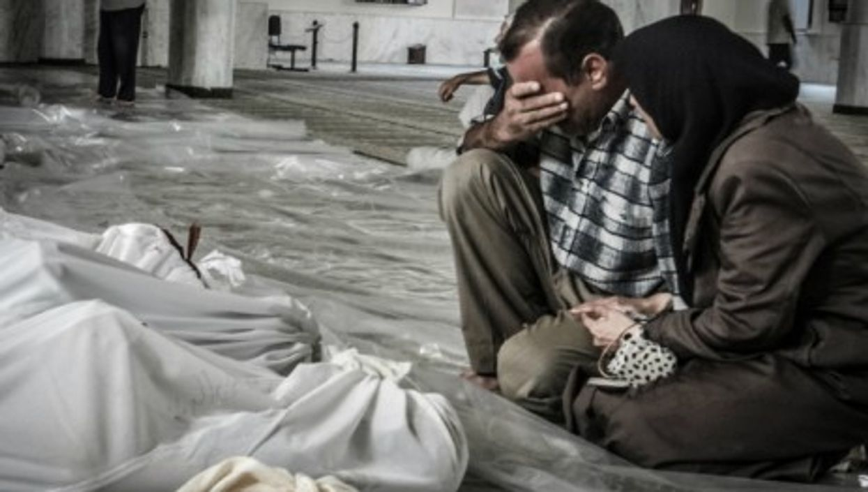 A mother and father weep over the body of their child, killed in a suspected chemical weapons attack on Damascus
