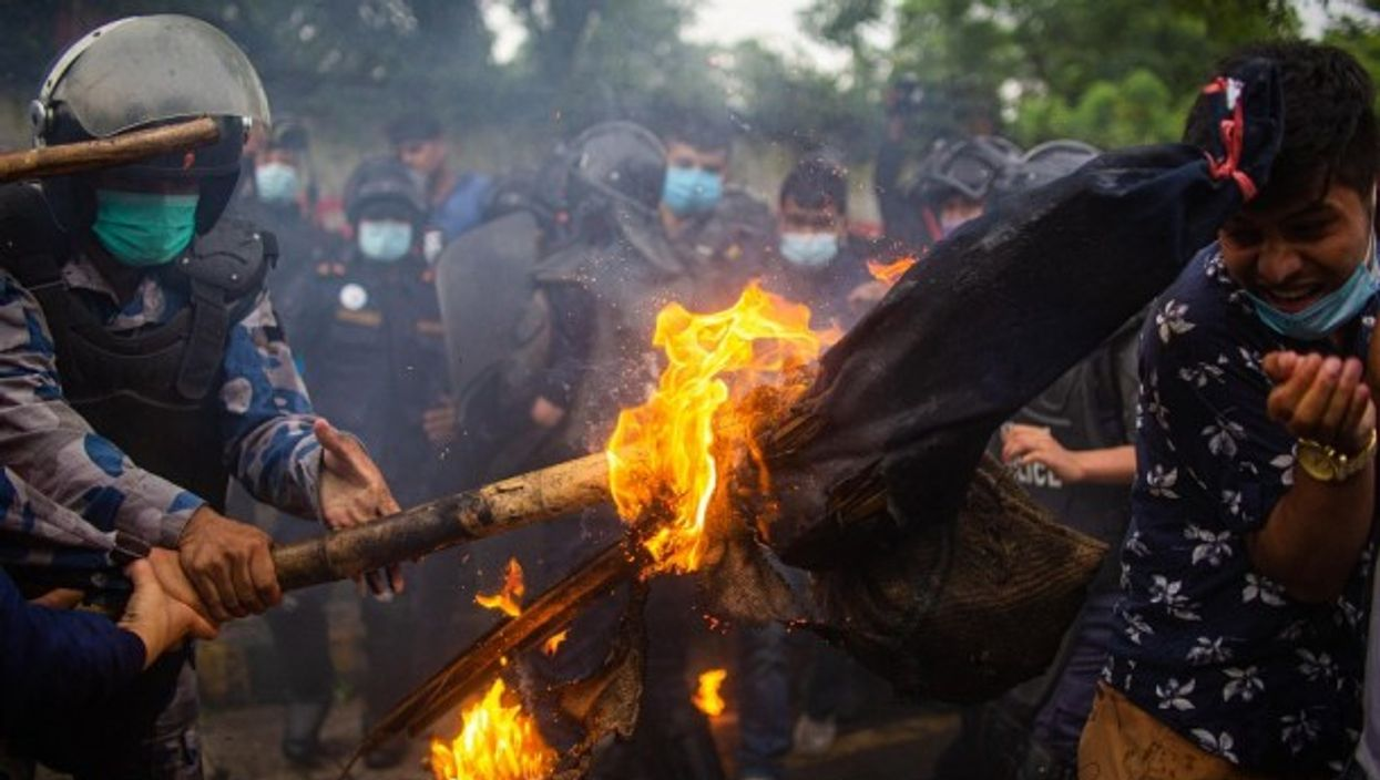 A Nepalese police officer douses burning effigy of PM during a protest in Kathmandu