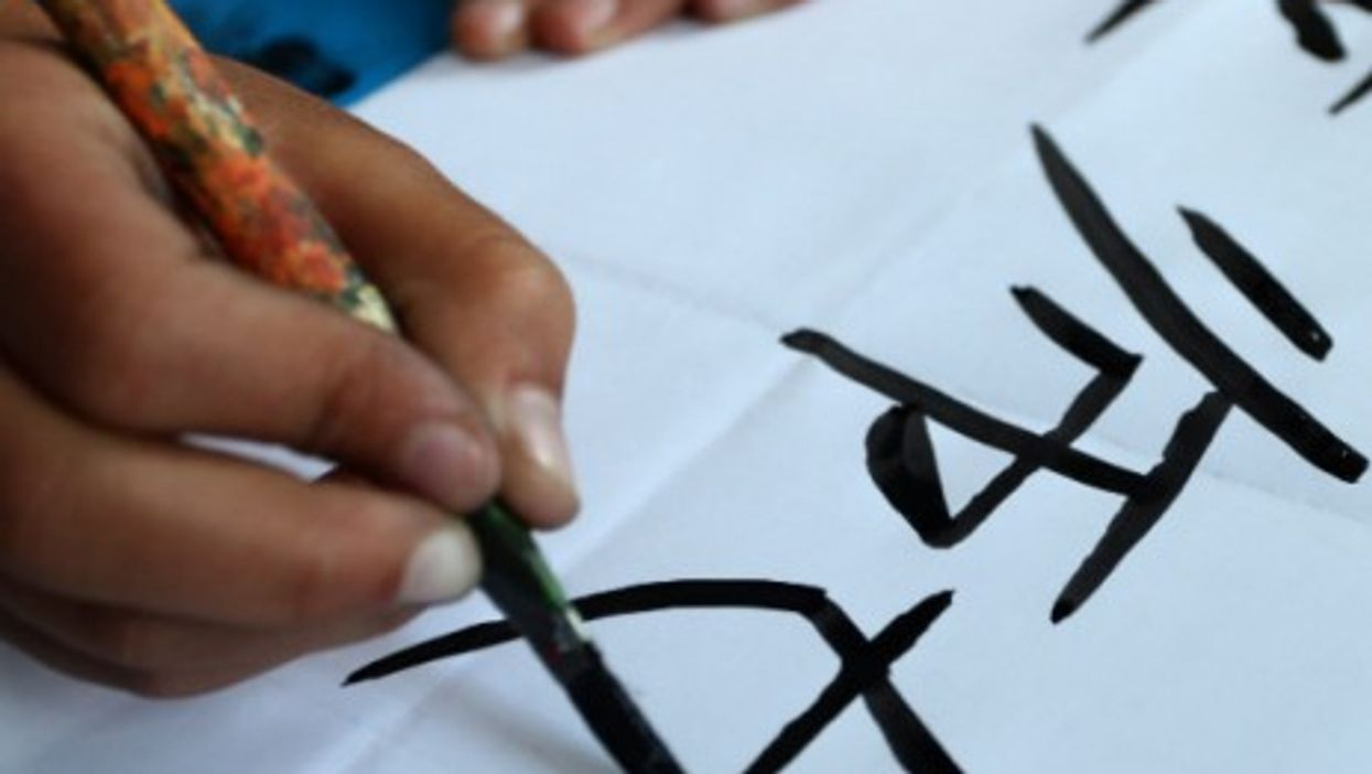 A Nepalese student writes Chinese characters in class in Kathmandu, Nepal, in April 2014.