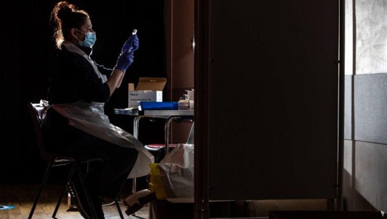 A nurse prepares the COVID-19 Oxford/AstraZeneca vaccine in the UK
