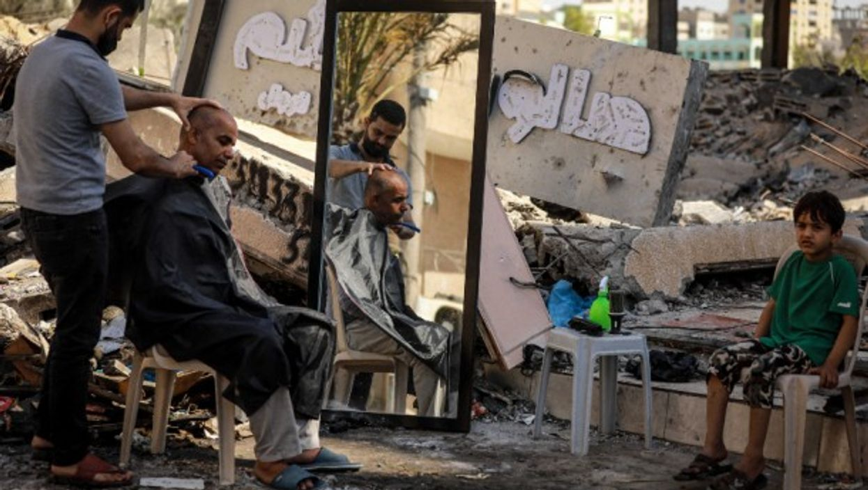 A Palestinian barber works among ruins of buildings and shops in Gaza City, on May 25