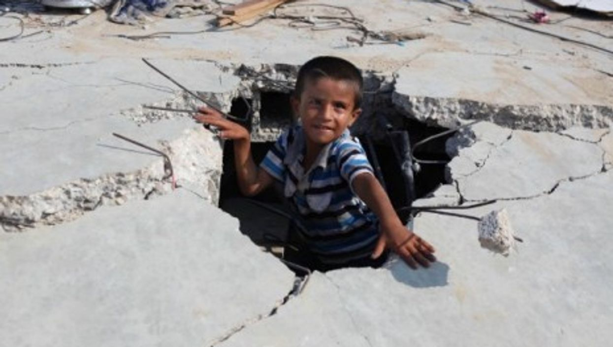 A Palestinian boy plays amid the rubble of his destroyed family home.