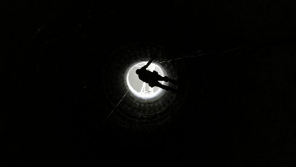 A Palestinian man in Rafah is lowered into a smuggling tunnel which connects Gaza and Egypt