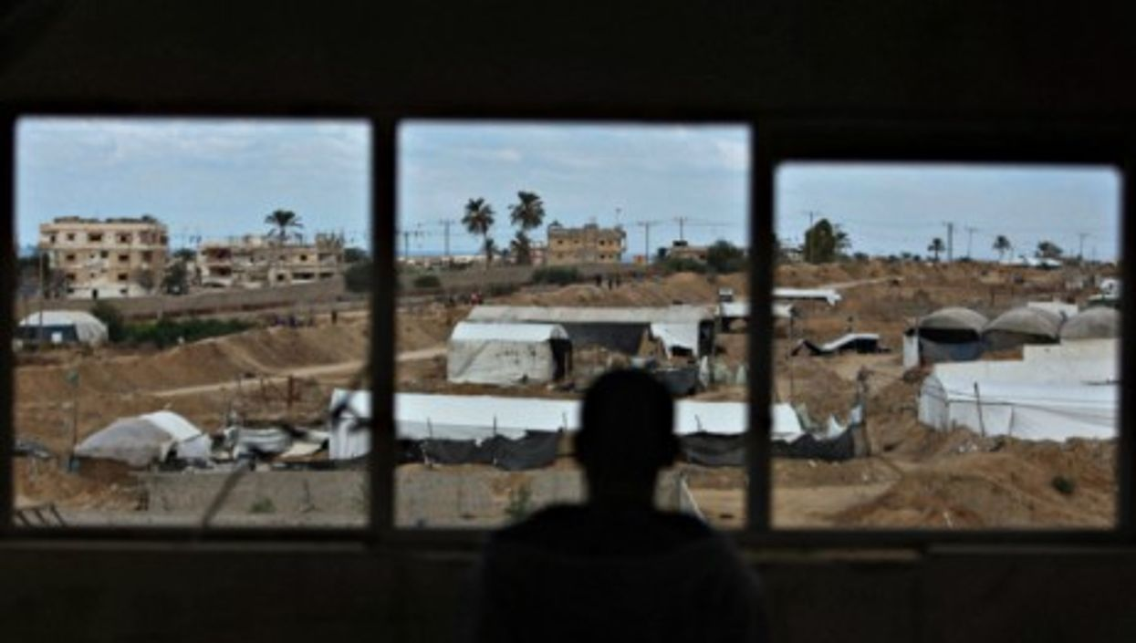 A Palestinian man looks on as an Egyptian military operation takes place in Rafah, Egypt.