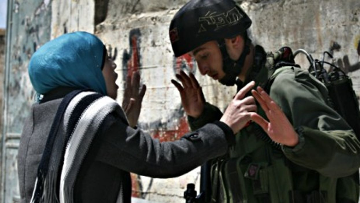 A Palestinian woman argues with an Israeli soldier in the West Bank village of Awarta