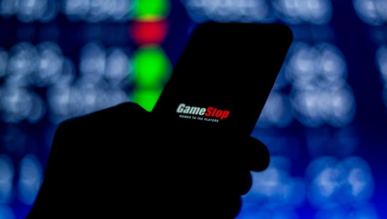 A person looks at the screen on their mobile phone, which shows the 'Gamestop' logo