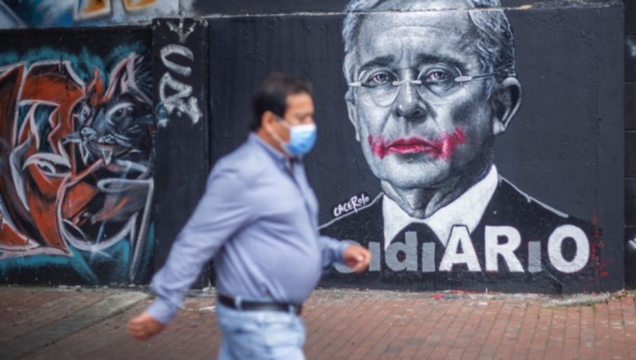 A person with a mask walking next to the image of former president Alvaro Uribe Velez in Bogota