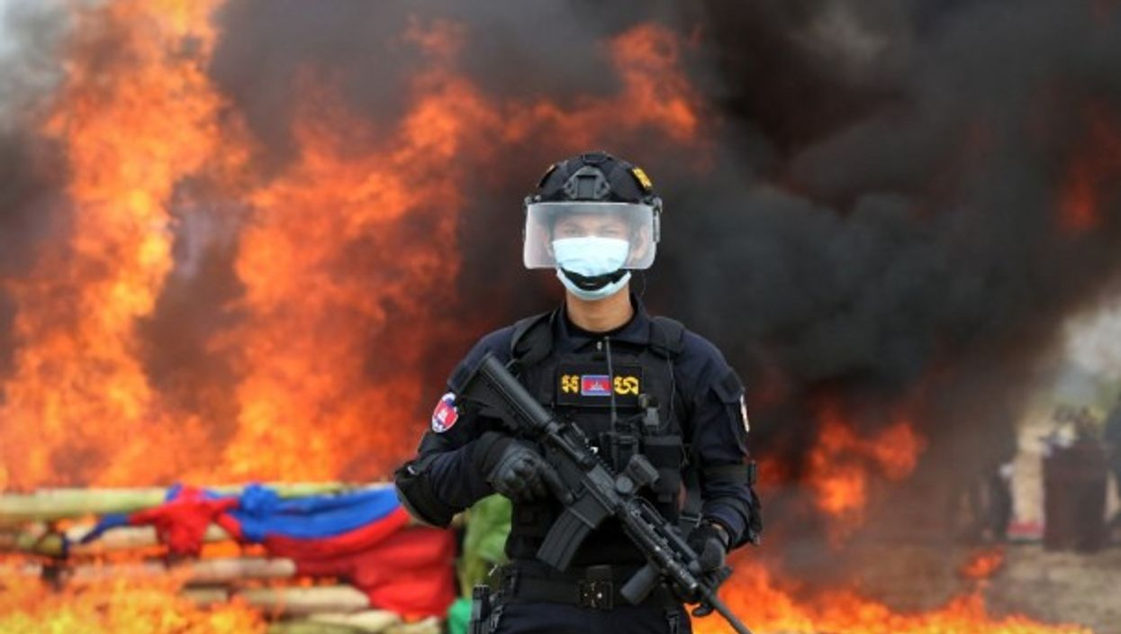 A police officer in Phnom Penh, Cambodia stands guard at a drug burning ceremony